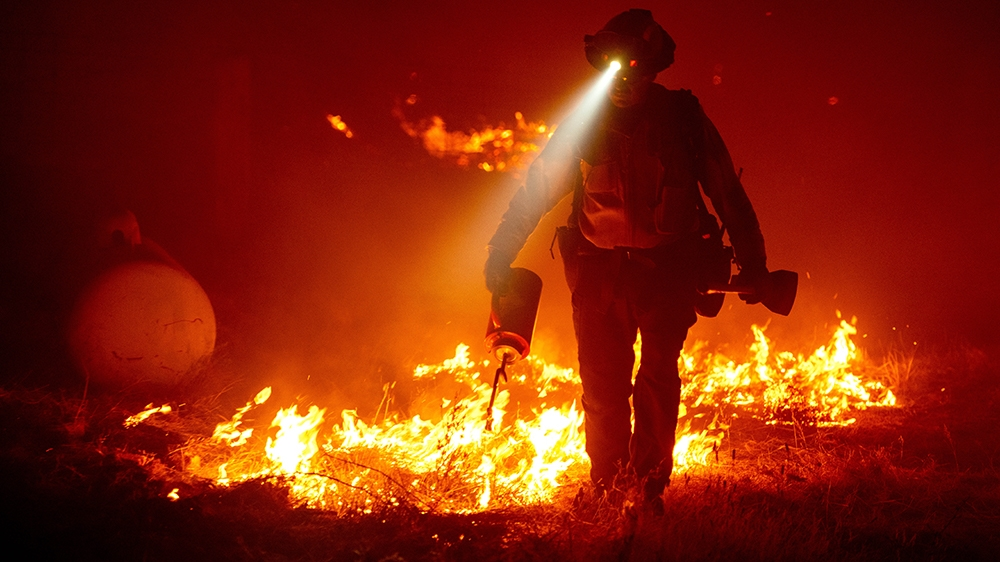 At least seven dead as dozens of wildfires rage across western US